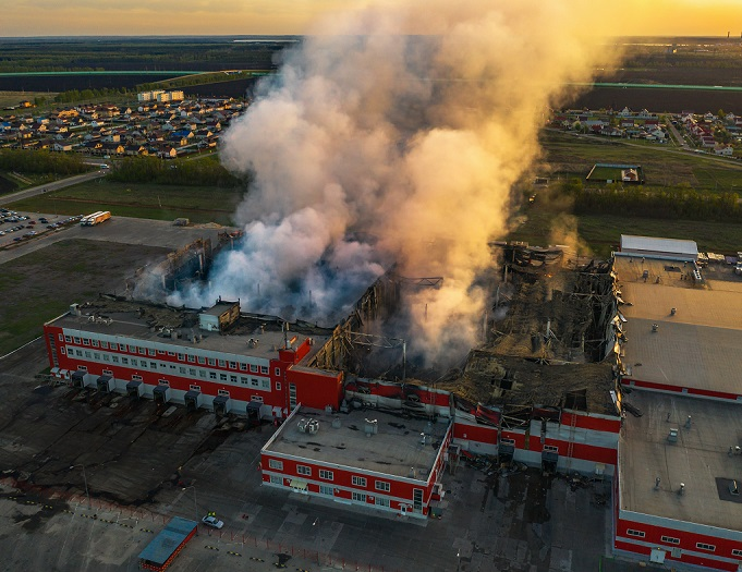 Burning industrial building with fire, huge thick smoke and burnt roof, aerial view